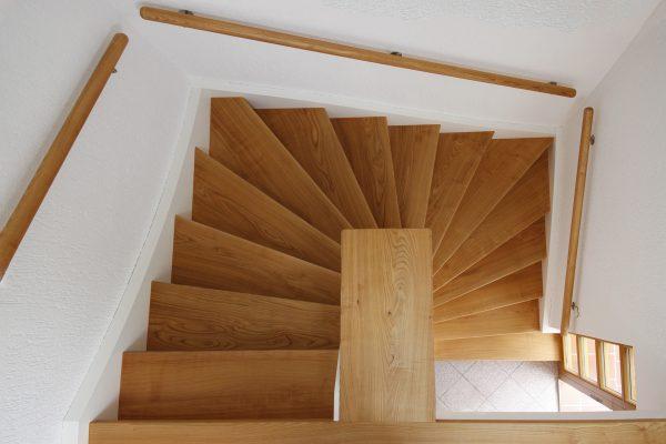 Holzstufen und Handlauf in Kirschbaum geölt, auf Betontreppe verklebt sowie weisse Blendwangen an den Wandseiten montiert