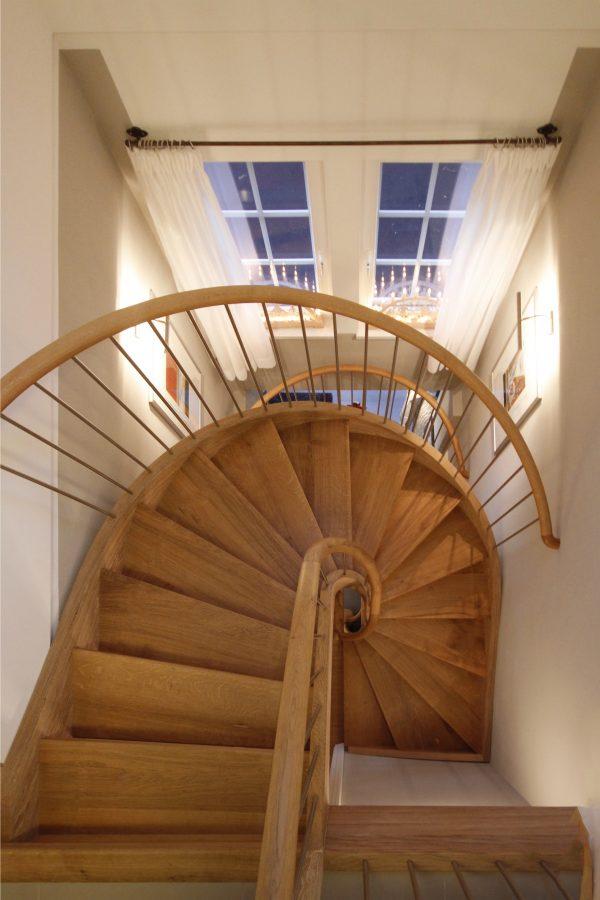 Halbgewendelte Holztreppe mit schichtverleimten Eichewangen, Massivkrümmling und Edelstahlgeländer, Podest in Tischlerplatte mit sternförmig angeordneter Deckschicht