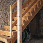 gerade Treppe in Lärchenholz, Stufen aus geachteltem Baumstamm hergestellt und auf 2 Holzbalken aufgesattelt, Oberfläche sägerauh und geölt, Geländer mit Handlauf und 2 Zwischengurten, Steinblock als Blockstufe für den Treppenanfang